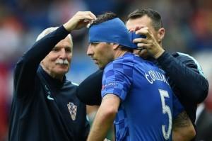 Il povero Ćorluka al secondo cambio di turbante, intonato al colore della maglia: ma non era meglio una cerniera a sto punto?