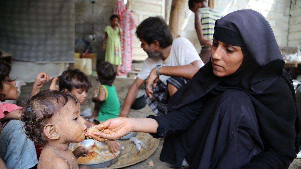 una donna nutre il figlio in un campo in Yemen